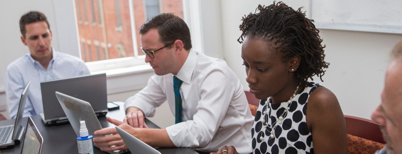 Law students take notes on a laptop while meeting with clients.