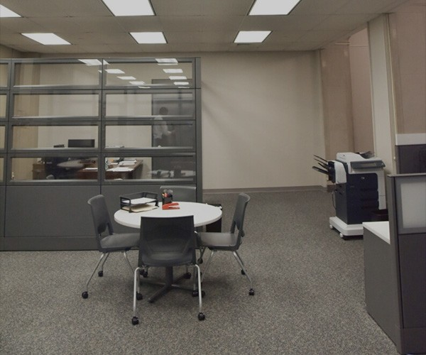 An office space with a round table, 4 chairs and a desk behind a glass screen